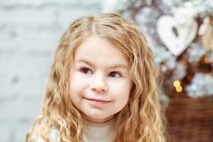 Adorable blond little girl sitting under the christmas tree and dreaming Stock Photos