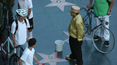 Tourists gather around a street performer in Hollywood at sunset in Hollywood. Stock Footage