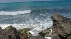 Stones at beach touched by slow waves Stock Footage