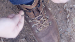 Man lacing up walking boots Stock Footage
