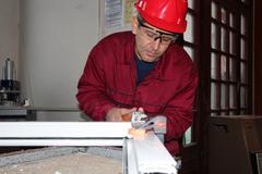 Worker Using Electric Grinder  - stock photo