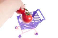 Hands putting tomatoes into shopping-cart - stock photo