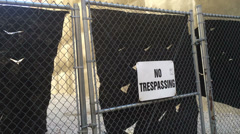 No Trespassing Sign on a Closed Fence Gate 4011 Stock Footage