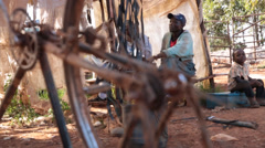 Focus shifts through spokes of bicycle of African Male in Background Stock Footage