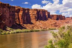 colorado river rock canyon reflection green grass outside arches national par - stock photo