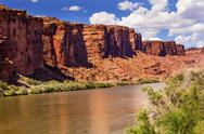 Stock Photo of colorado river rock canyon reflection green grass outside arches national par