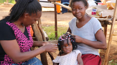 Two women weave a child's hair at open market Stock Footage
