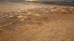 Tilt shot from bootprints in the sand to sunset over razor wire barrier Stock Footage