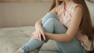 Happy young woman sitting on sofa using cell phone looking at camera and smiling Stock Footage