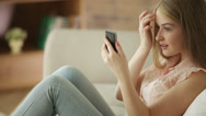 Funny girl sitting on sofa looking in mobile phone like in mirror and smiling Stock Footage