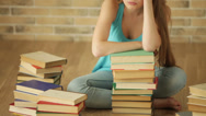 Stock Video Footage of Tired girl sitting on floor with stack of books and looking at camera. Panning