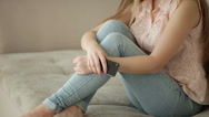 Young woman sitting on couch using mobile phone looking at camera and smiling Stock Footage