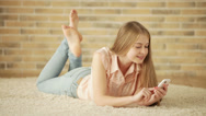 Beautiful girl lying on carpet using mobile phone looking at camera and smiling Stock Footage