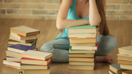 Stock Video Footage of Bored student girl sitting on floor with pile of books and looking at camera.
