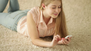 Charming girl lying on carpet using mobile phone and smiling. Panning camera. Stock Footage