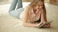 Stock Video Footage of Cute girl lying on floor using touchpad looking at camera and smiling. Panning