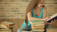 Stock Video Footage of Charming girl sitting on floor reading book and smiling. Panning camera