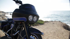 Motorbike is standing on the seashore cliff harley davidson motorcycle beach Stock Footage