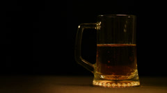 Pour the beer into a glass on a black background Stock Footage