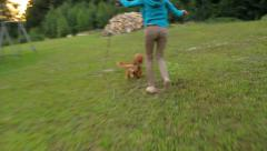 Happy girl and dog playing in the garden in summer Stock Footage