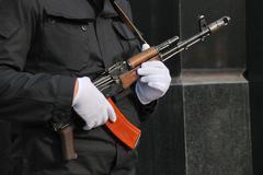 Hands in white gloves with a kalashnikov Stock Photos