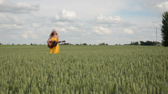Country woman with smile walk and play guitar in wheat field Stock Footage