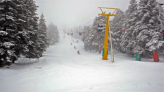 Snowy day in the mountain and ski lift moves up with skiers. Stock Footage