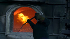 Stock Video Footage of worker stirred liquid aluminum in the furnace of slow motion burner aluminum