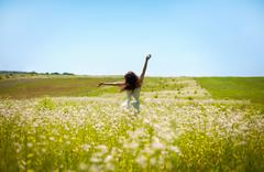 girl lifting her hands up in the air runs across the field - stock photo