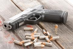 handgun and bullets lying on a wooden table - stock photo