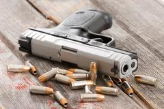 handgun with scattered bullets and cartridges - stock photo