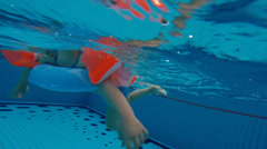 Chinese girl playing inside swimming pool Stock Footage