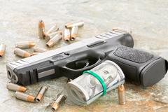 handgun with money and scattered bullets - stock photo