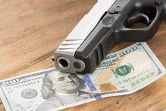 muzzle of a gun with a 100 dollar bill - stock photo