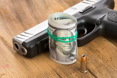 handgun with a roll of dollar bills and a bullet - stock photo