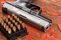 Close up of a handgun and rack of ammunition Stock Photos