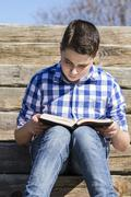 Learn.young boy reading a book in the woods with shallow depth of field and c Stock Photos