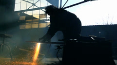 Worker melting iron hot sparks repel from the ground in slow motion effect. - stock footage