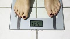Woman on weight scales Stock Footage