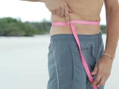 Slim man measuring his waist with tape outdoors NTSC - stock footage