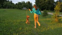 Girl and dog running in the garden, spend a free time Stock Footage