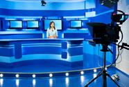 Stock Photo of television newscaster at blue tv studio