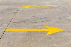 Yellow traffic arrow on concret road Stock Photos