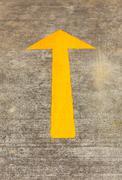 yellow traffic arrow on concret road - stock photo