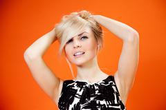 Charming blonde is looking at you! lady against orange background Stock Photos