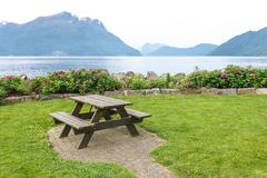 Table and benches for picnic on fjord shore - stock photo