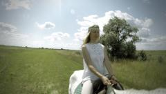 Young female sitting on the white horse outdoor under sky with clouds - stock footage
