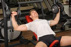 handsome young man doing dumbbell incline bench press workout in gym - stock photo