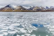 Stock Photo of the seasons last remaining shore fast ice in bellsund, spitsbergen, svalbard