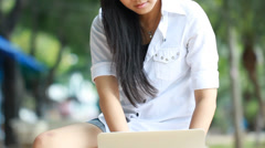 Asian woman on laptop outside Stock Footage